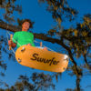 tree swing with large skateboard like deck that you can stand on and swing