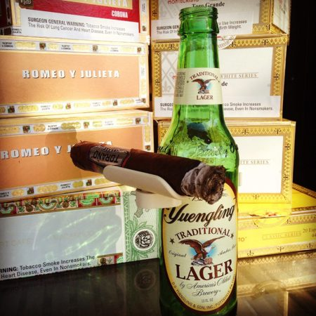 accessory for beer bottle that assists in holding a cigar
