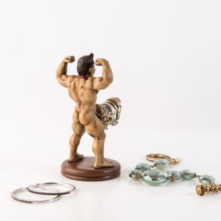 very buff naked man figurine with a very large penis used as a ring or jewelry holder